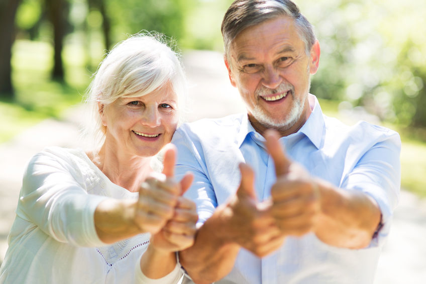 couple showing thumbs up and smiling